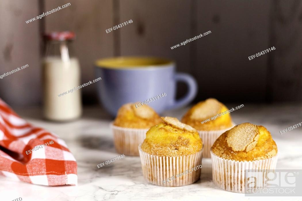 Stock Photo: four delicious cupcakes, milk bottle, blue ceramic cup and napkin on marble table on wooden background.