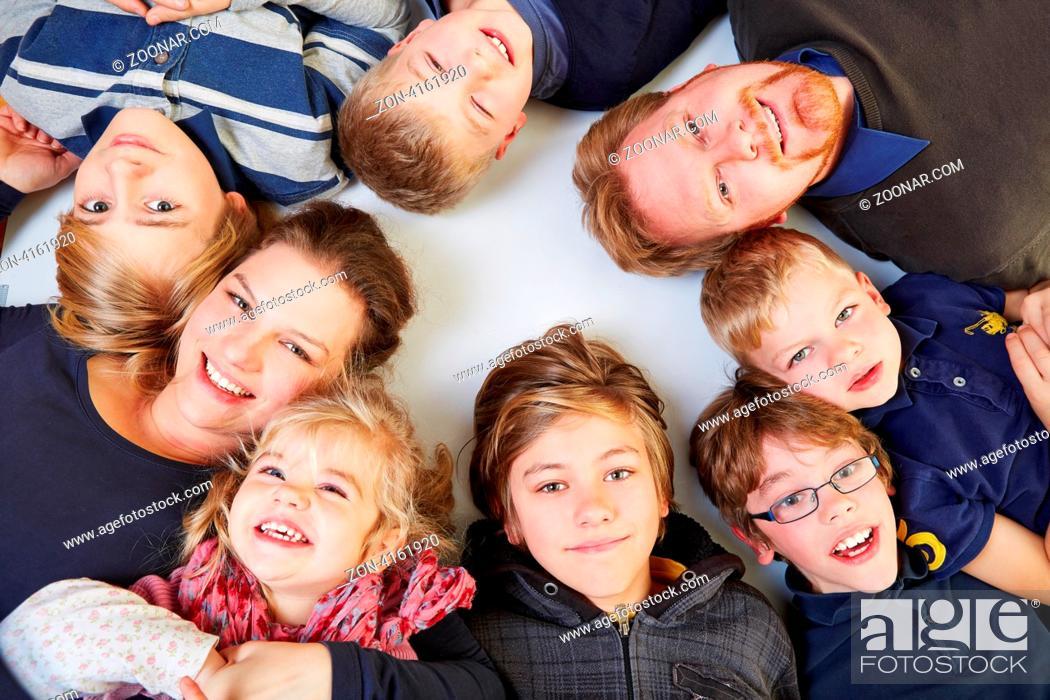 Stock Photo: Kinderreiche Familie liegt lachend im Kreis und schaut hoch.