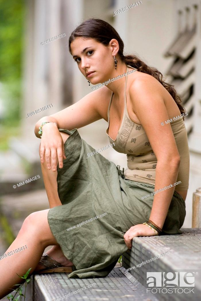 Stock Photo: A beautiful young model sits on the steps on an old disused building.