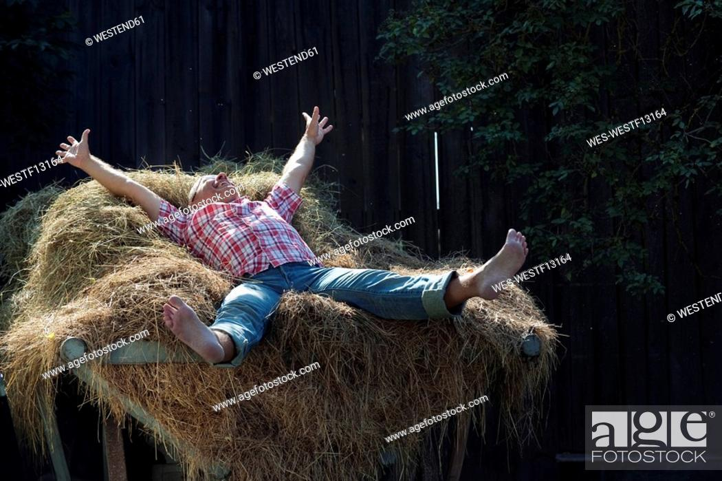 Stock Photo: Germany, Bavaria, Senior man lying on haystack.