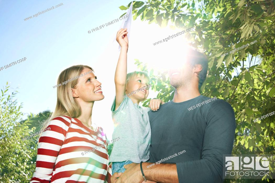 Stock Photo: Germany, Cologne, Family playing with paper plane, smiling.