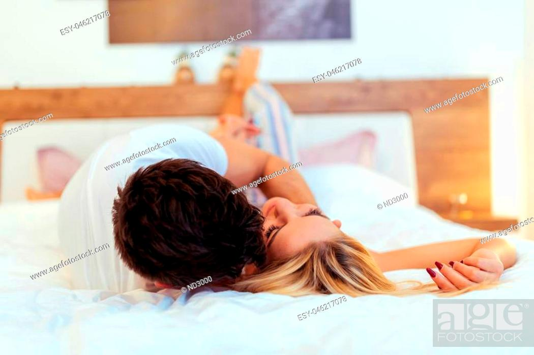 Stock Photo: Couple sensual foreplay in bed while lying on bed.