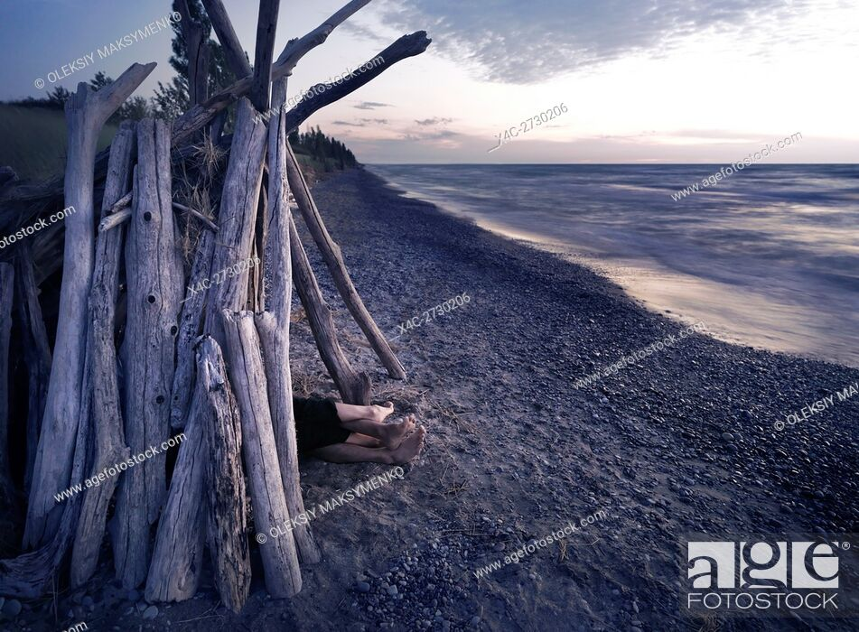 Stock Photo: Feet of a couple under a driftwood shack alone on a sea shore at sunset.