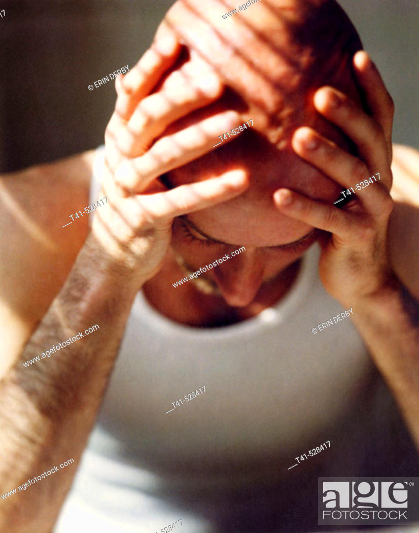 Stock Photo: 40 year old, bald man leans over his morning paper.