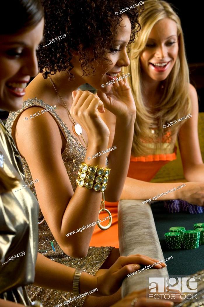 Stock Photo: Young women gambling, smiling, side view.