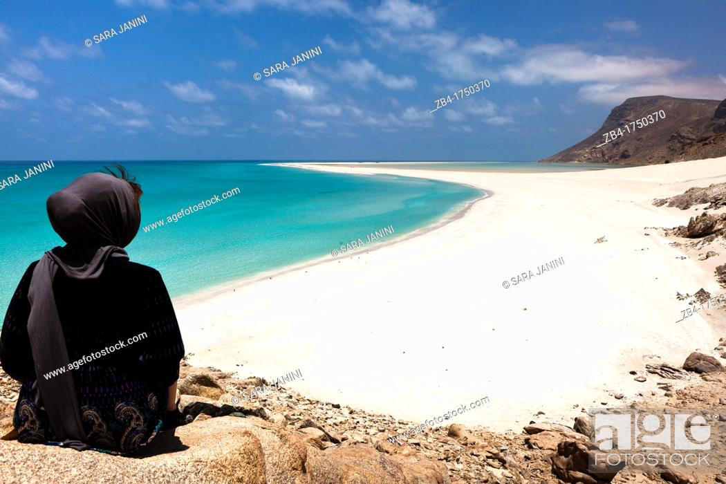 Stock Photo: A tourist sitting on a top rock viewing the sand bar on the seaward edge of Ditwah lagoon near Qalansiyah, Socotra island, listed as World Heritage by UNESCO.