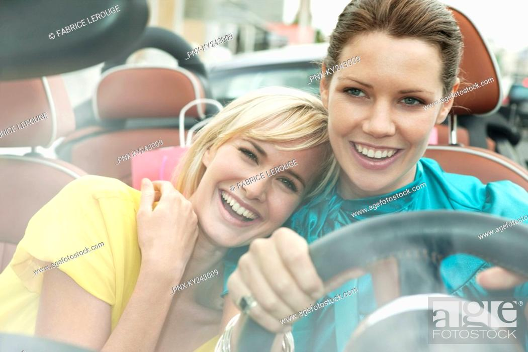 Stock Photo: Two women sitting in a car after shopping.
