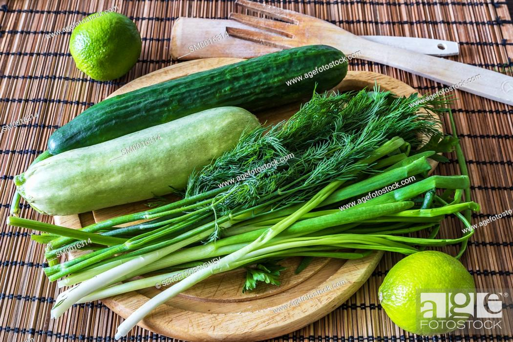 Stock Photo: Cucumber, zucchini, greens, limes and a cutting board lie on the kitchen table.