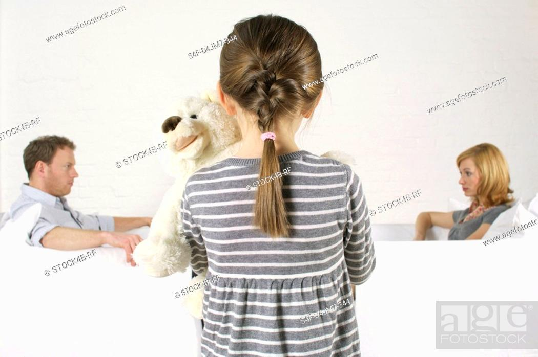 Stock Photo: Frustrated couple sitting vis-a-vis, girl holding teddy bear standing in foreground.