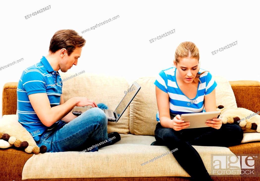 Imagen: Young couple relaxing on sofa and using tablet and laptop.