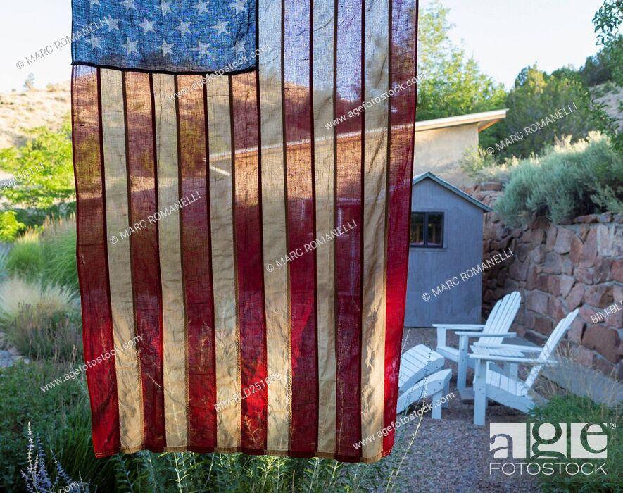 Photo de stock: American flag hanging near house.