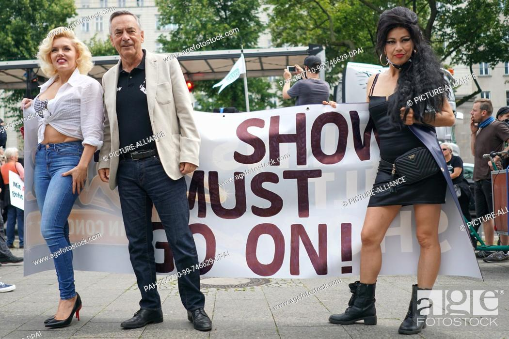 """Stock Photo: 10 July 2020, Berlin: Bernhard Kurz, producer, and Suzy (l) and Rachel, two performers from the Estrel Hotel, hold a poster with the words """"""""The Show must go on."""