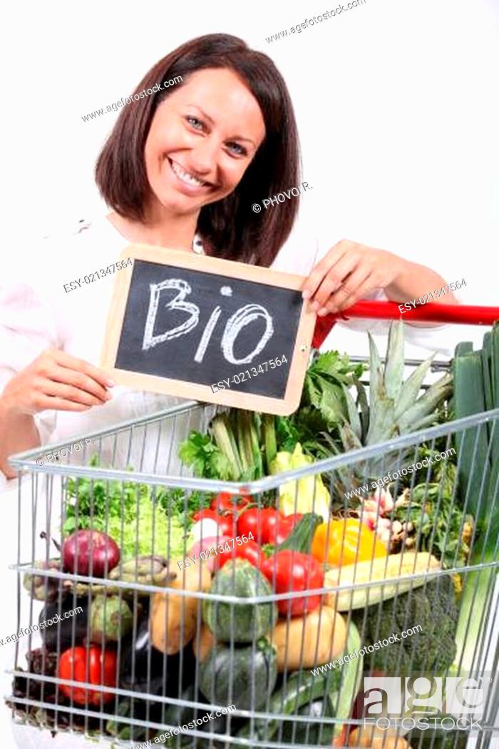 Stock Photo: Woman with a trolley of organic vegetables.