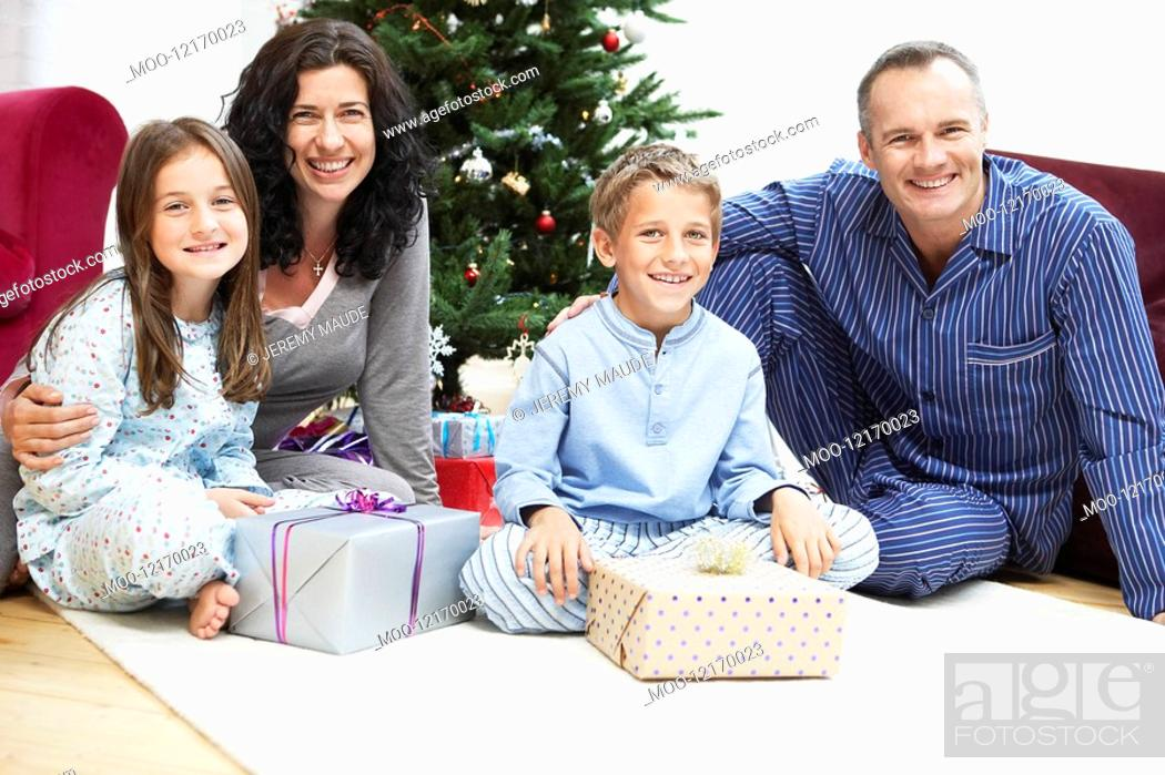Stock Photo: Happy Family in Front of Christmas Tree portrait.