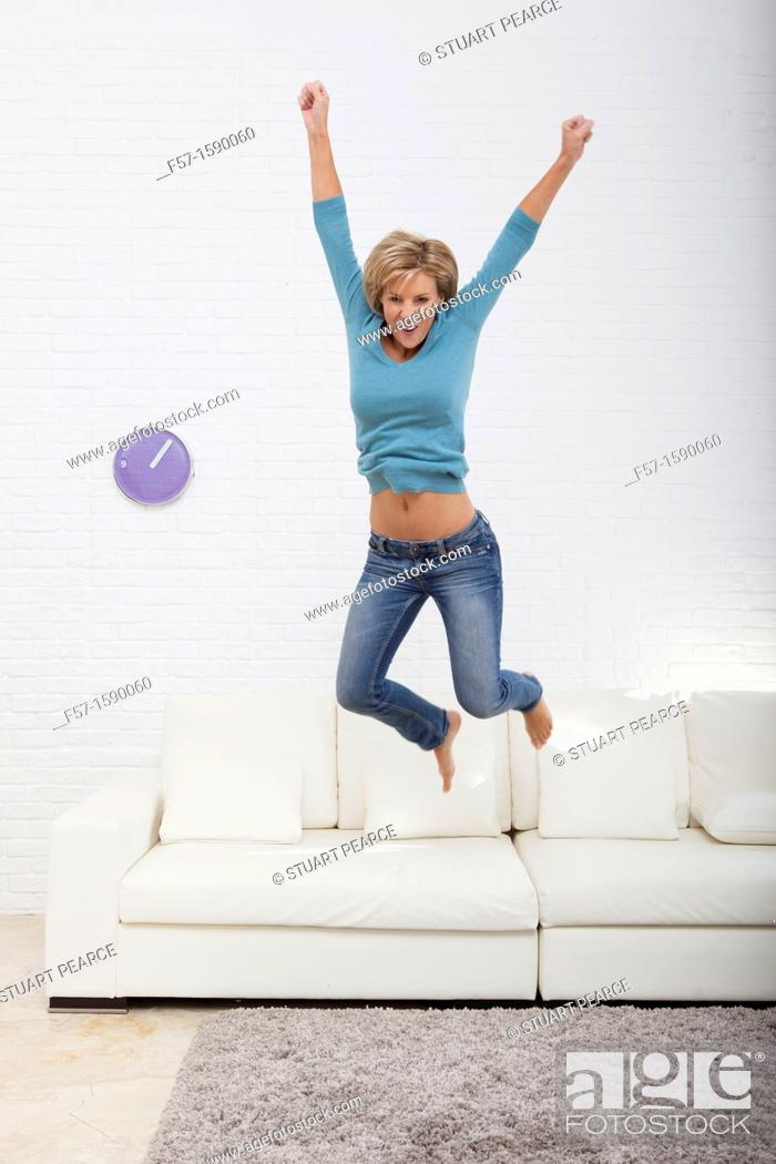 Stock Photo: Young woman jumping for joy off her sofa.