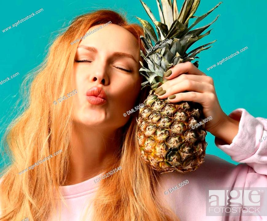Stock Photo: Young happy beautiful sexy woman posing laughing with pineapple fruit on a blue mint background.