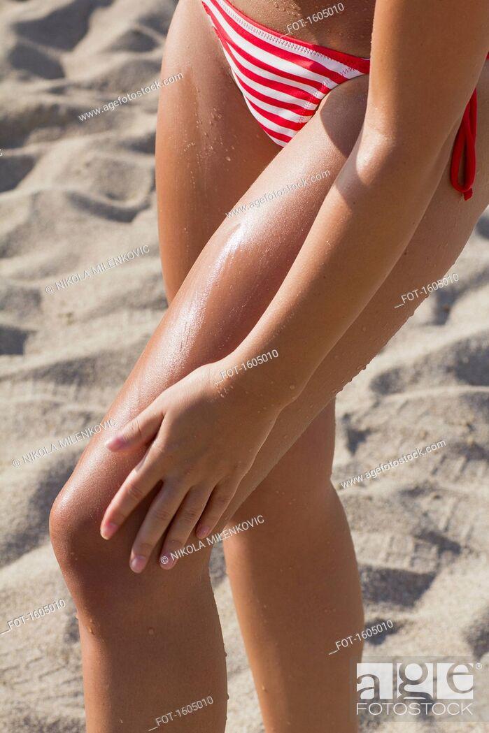 Photo de stock: Low section of woman wearing bikini standing on beach.