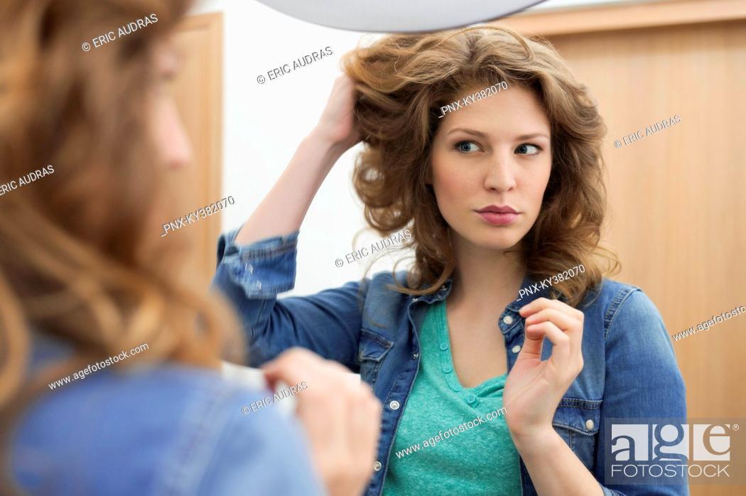Stock Photo: Woman examining her hair.