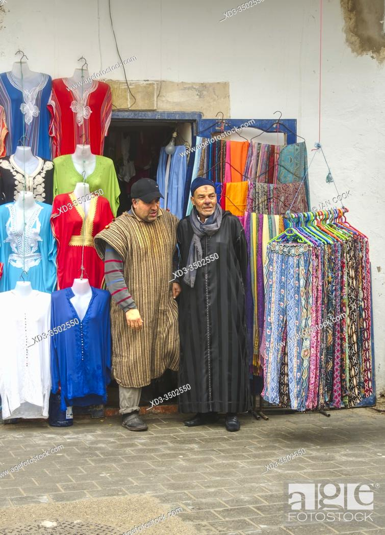 Stock Photo: two men in tradidional dress coming out of a shop, Essaouira, Morocco.