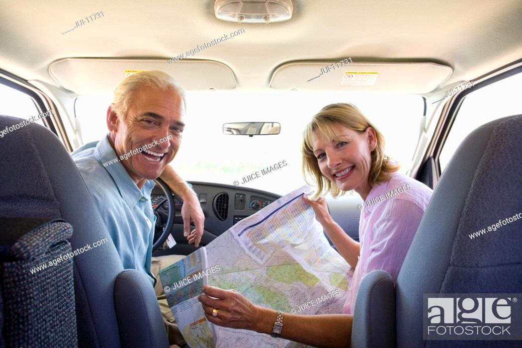 Stock Photo: Mature couple with map in motor home, smiling, portrait.