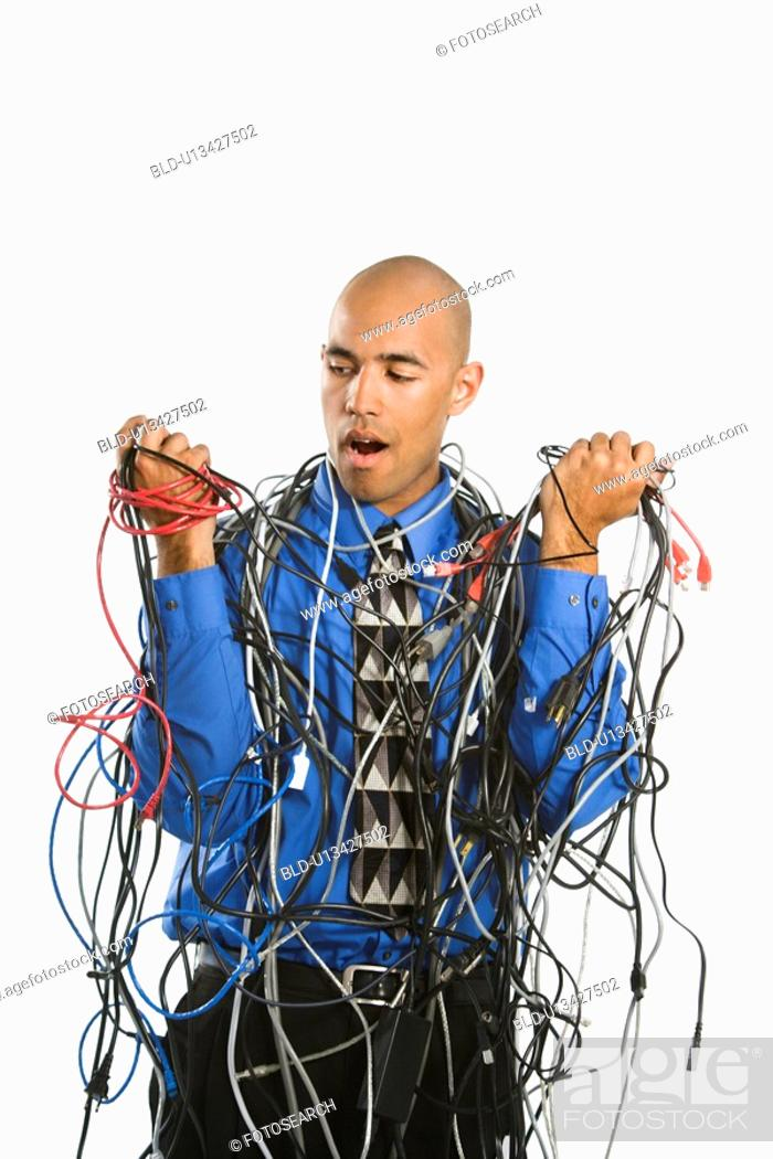 Stock Photo: Confused businessman tangled in cables.