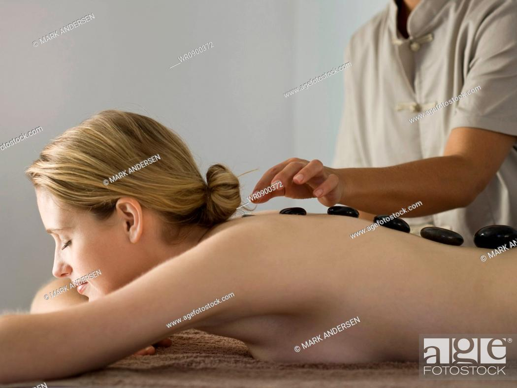 Imagen: Woman placing black stones on womans spine.