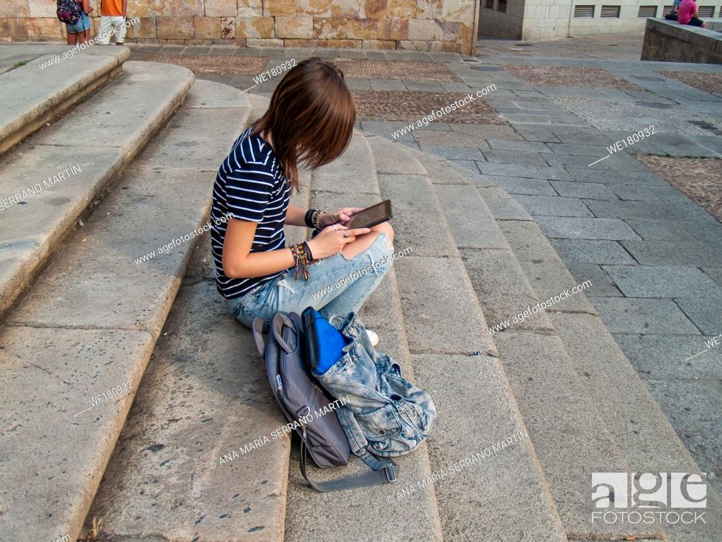 Imagen: A teenage woman with a tablet on the stairs of a university in a university campus.