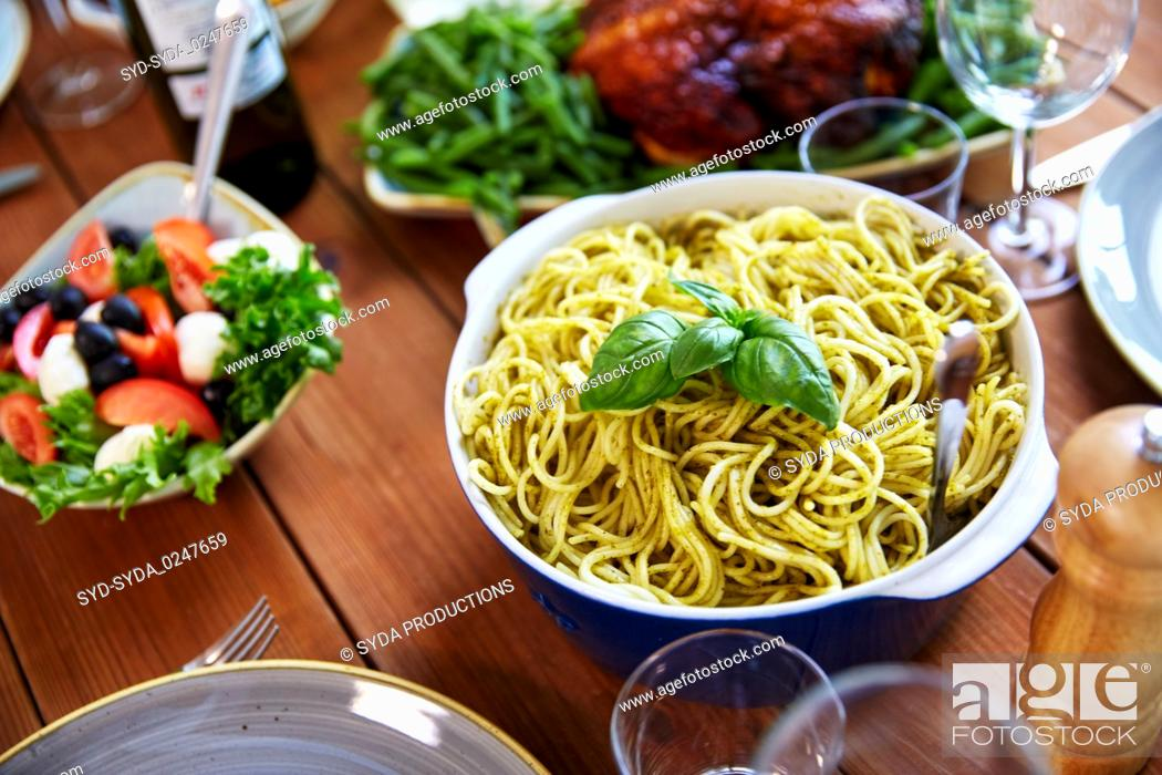 Stock Photo: pasta with basil in bowl and other food on table.