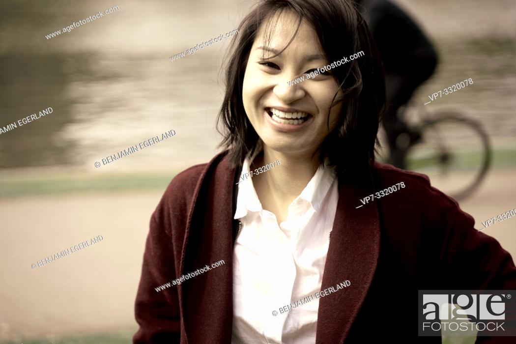 Stock Photo: smiling Asian woman outdoors in city, in Frankfurt, Germany.