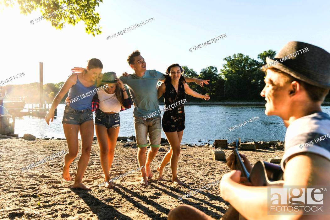 Stock Photo: Group of friends having a party at the riverside.