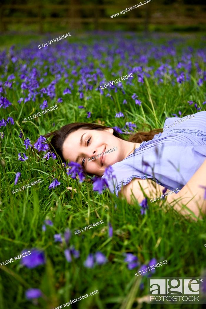 Stock Photo: A young woman lying amongst bluebells, smiling.