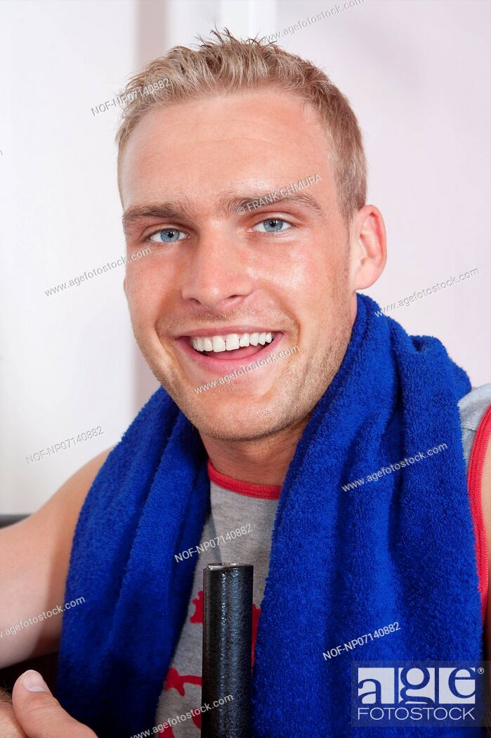 Stock Photo: portrait of a young man with towel in modern gym.