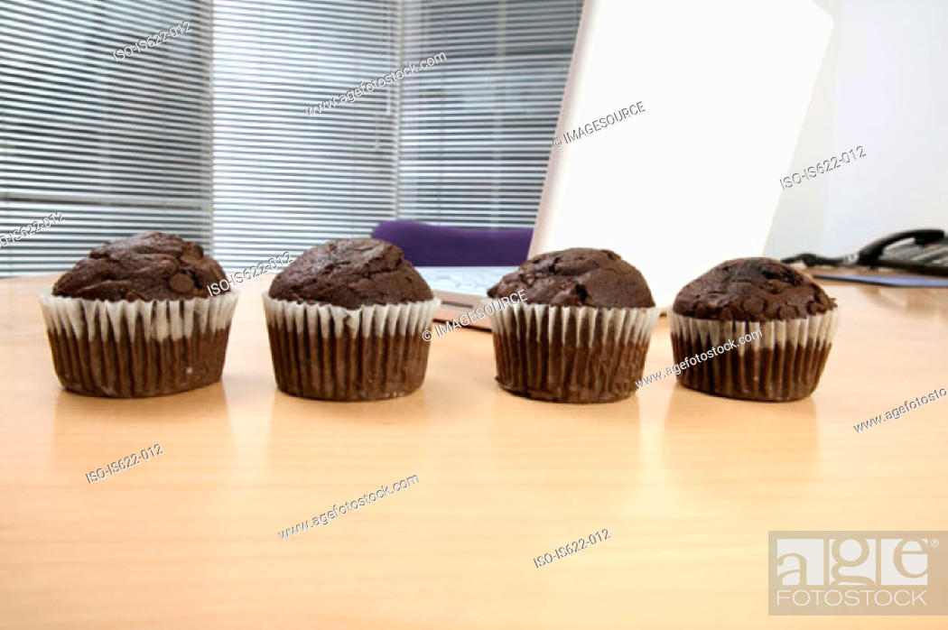 Stock Photo: Chocolate muffins on desk.