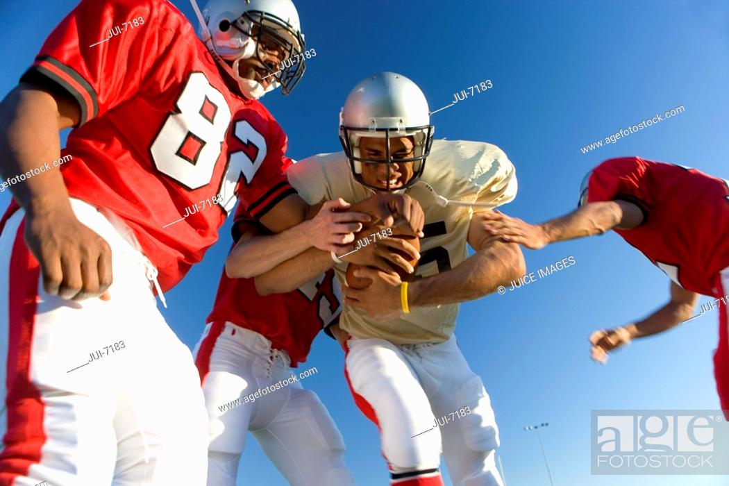 Stock Photo: American football players tackling opposing player with ball, low angle view.