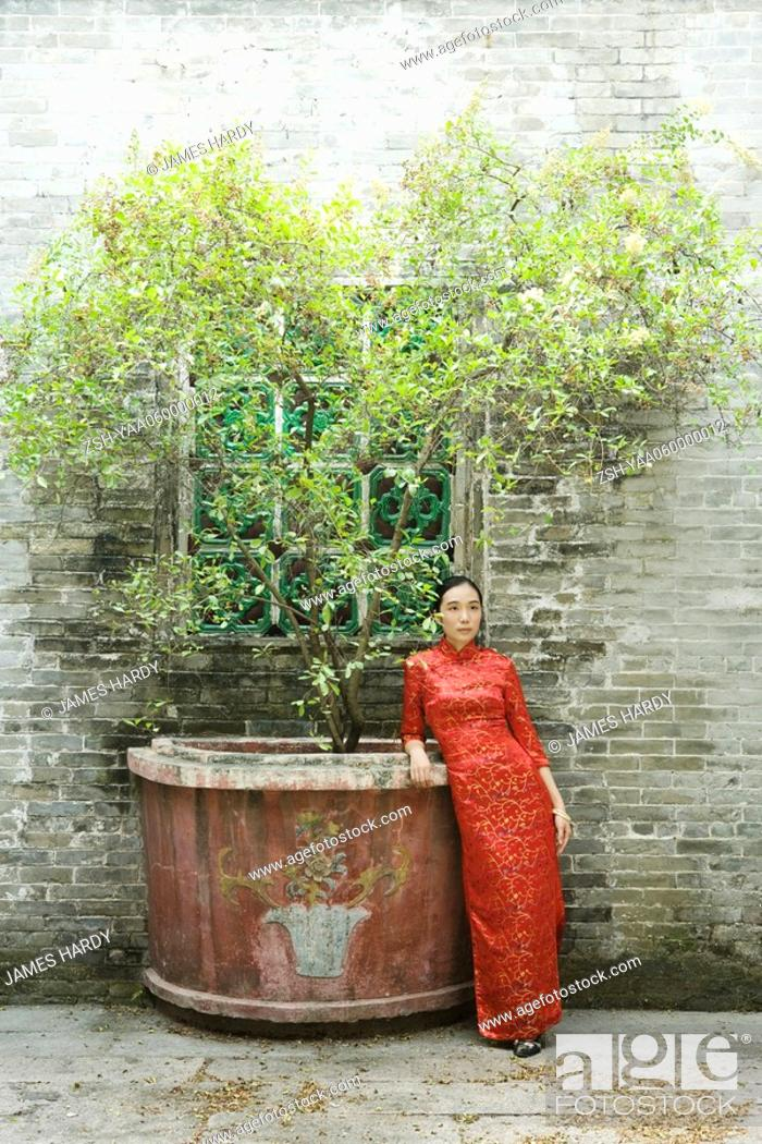 Stock Photo: Young woman dressed in traditional Chinese clothing, standing next to potted tree.