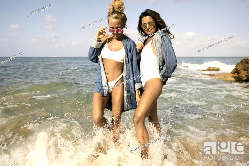 Photo de stock: Two women standing in water at beach, Chersonissos, Crete, Greece.