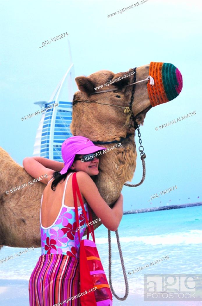 Stock Photo: Western tourist hugging a camel on the beach in Dubai, United Arab Emirates.
