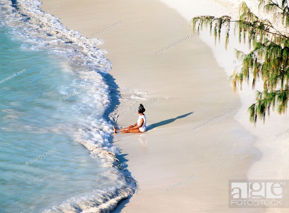 Imagen: Waves break on white sand beach  Young woman relaxing at Jolly Beach, Coco Beach, west coast of Caribbean island of Antiqua.