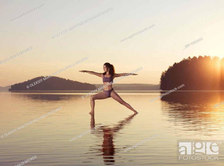 Stock Photo: Young woman practicing Hatha yoga on a floating platform in water on a lake during sunrise, Yoga Warrior posture, Veerabhadrasana.