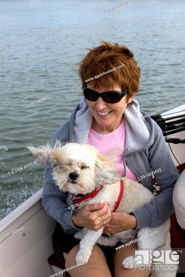 Stock Photo: Woman and her dog riding in a boat on the Intracoastal waterway in Crescent Beach, FL, USA.