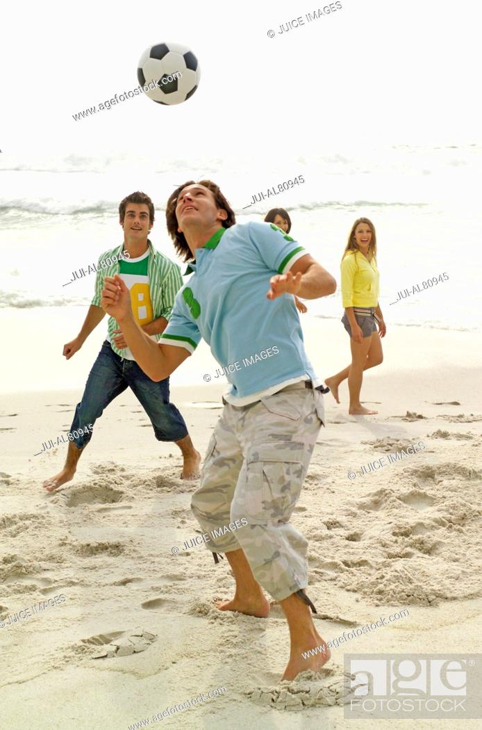 Stock Photo: Friends playing with soccer ball at beach.