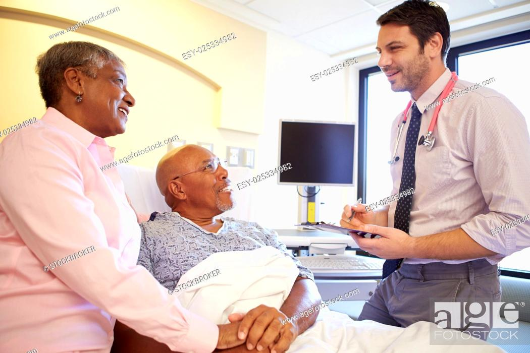 Stock Photo: Doctor Talking To Senior Couple On Ward.