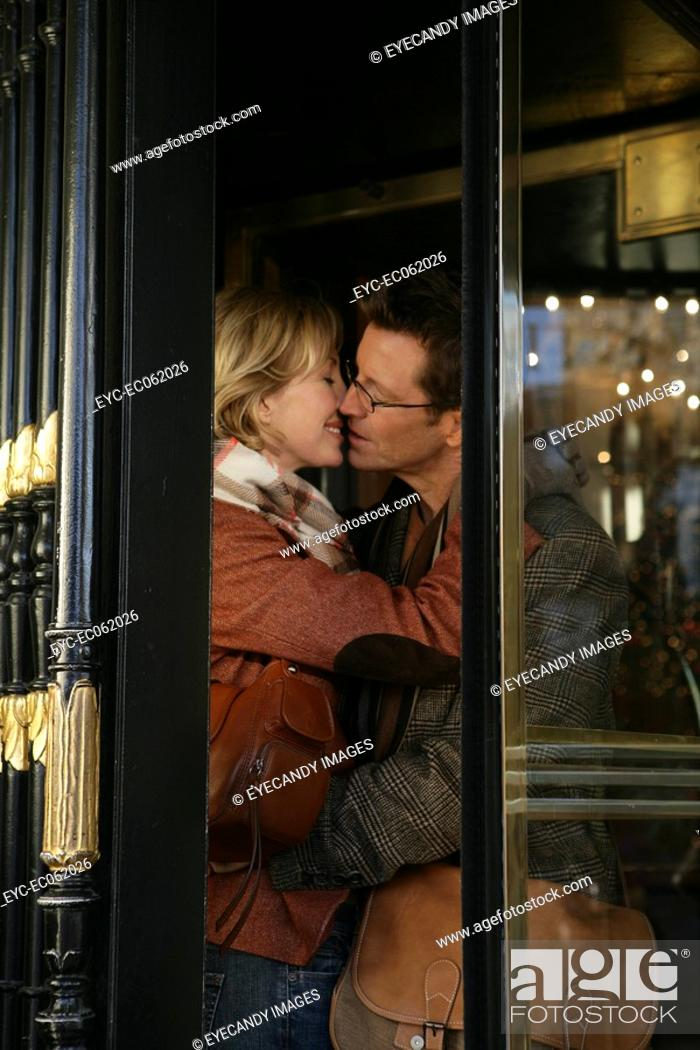 Stock Photo: Mature couple kissing inside revolving doors.
