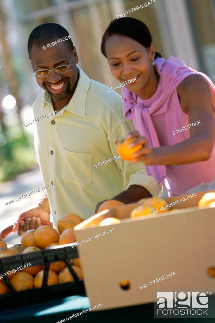 Stock Photo: Young couple picking oranges from a shop in a market.