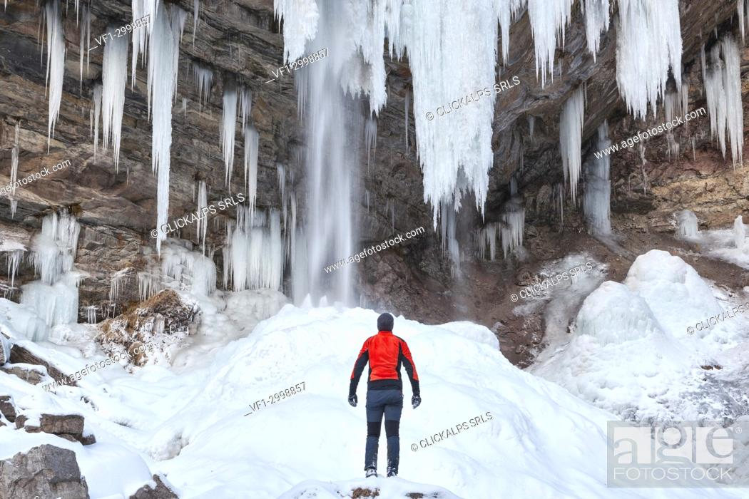 Stock Photo: Man in front of Waterfall of Hell (Cascata dell' Inferno) in the San Lucano valley, Taibon Agordino, Belluno, Veneto, Italy.