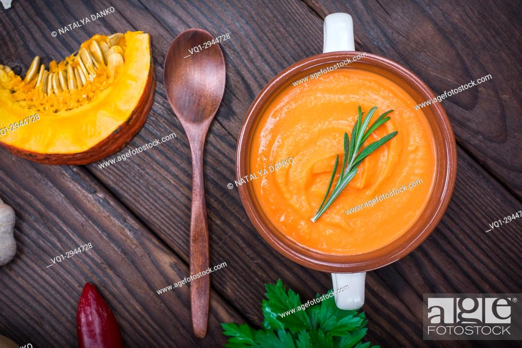 Stock Photo: creamy pumpkin soup in a ceramic plate with a wooden spoon on the table, top view.