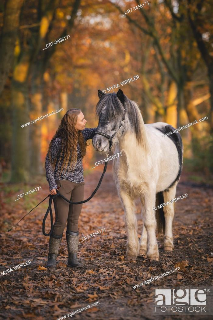 Stock Photo: Young woman with her icelandic horse enjoying a warm autumn day outside in Noord-Brabant, The Netherlands.