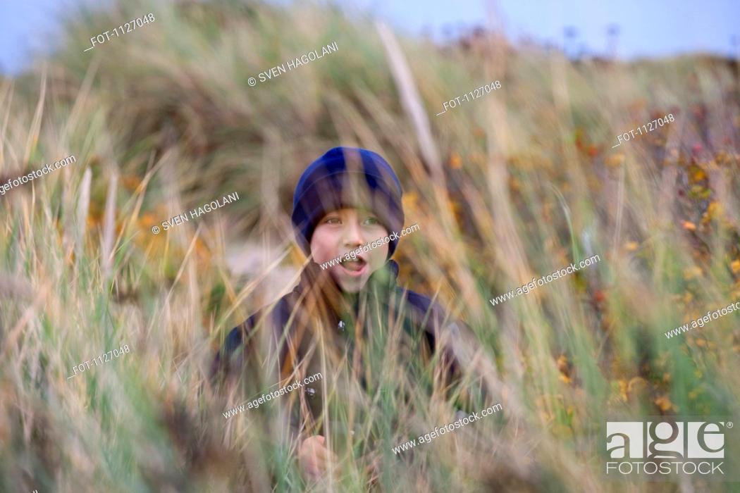 Stock Photo: Boy among the beach grass.
