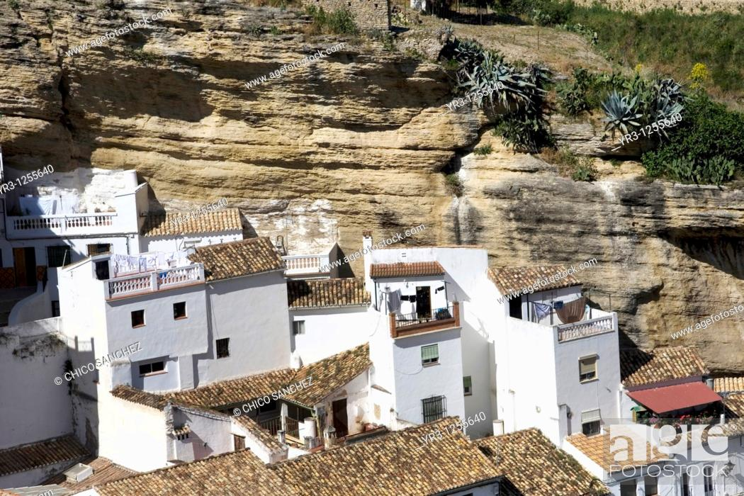Stock Photo: White homes constructed in caves sit under huge rocks in Setenil de las Bodegas village, Cadiz province, Andalusia, Spain.