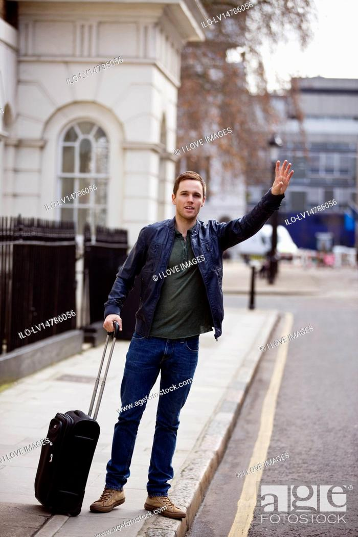 Stock Photo: A young man with his suitcase, hailing a taxi.